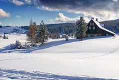 Winter Mountain Landscape In Sunny Day. Dark Clouds On Blue Sky. Settlement Jizerka Czech Republic Stock Photo