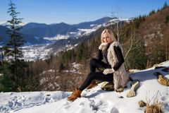 Beautiful blonde tourist girl sitting on the rock. royalty free stock photography