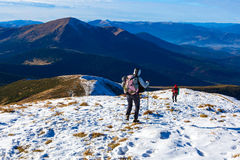 Winter Mountain Range View and Group of Trekkers Walking on Snow Trail royalty free stock images