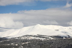 Winter mountain resort. A sunny day on a mountain resort wiyh peaks covered in snow Royalty Free Stock Photography