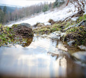 Winter at mountain river. Reflections of clouds in water level. Royalty Free Stock Photography