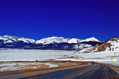Winter Mountain Road in Colorado. A winter road in Colorado with snow capped Rocky mountains Royalty Free Stock Images