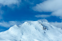 Winter mountain top view (Austria). Hillside undulate ski tracks and clouds in the blue sky. Winter Austria Stock Images