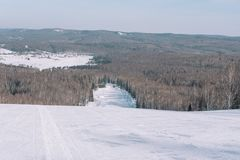Winter mountain view from above. View down from the mountain in winter. Winter landscape. Winter in Siberia. Trees grow down below stock photos