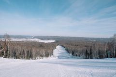 Winter mountain view from above. View down from the mountain in winter. Winter landscape. Winter in Siberia. Trees grow down below royalty free stock images