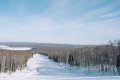 Winter mountain view from above. View down from the mountain in winter. Winter landscape. Winter in Siberia. Trees grow down below stock image