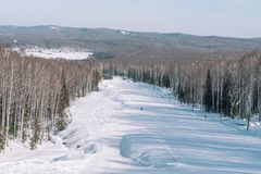 Winter mountain view from above. View down from the mountain in winter. Winter landscape. Winter in Siberia. Trees grow down below royalty free stock photography