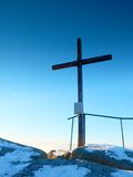 Winter mountain. Wooden cross on rocky mountain summit. Sharp peak covered by ice and snow.  Wooden unpretentious crucifix in memory of victims of mountains Stock Image