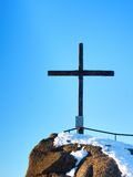 Winter mountain. Wooden cross on rocky mountain summit. Sharp peak covered by ice and snow.  Wooden unpretentious crucifix in memory of victims of mountains Royalty Free Stock Photography