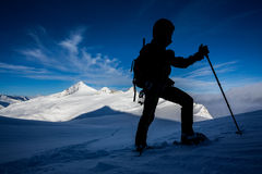 Winter mountaineering. Silhouette of a man doing a snowshoe mountain ascend Royalty Free Stock Photography