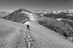Winter mountain landscape. Snow and female hiker at high altitude - Ciucas Mountains, landmark attraction in Romania Stock Photo