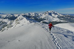 Winter mountain landscape. Snow and female hiker at high altitude - Ciucas Mountains, landmark attraction in Romania Royalty Free Stock Photo