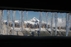 Winter in the mountains. View of the pyramid-shaped mountain through icicles Stock Photo
