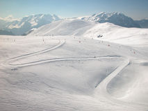 Winter in the mountains. Curving ski trail in the French Alps Royalty Free Stock Photos