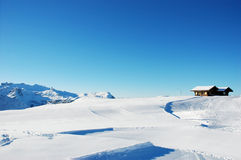 Winter mountains. Winter snowy Alps with two cabin and clear blue sky, Grindelwald in Bern Canton Switzerland Royalty Free Stock Photos