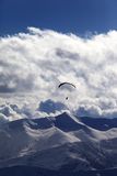 Winter mountains in evening and silhouette of paraglider Royalty Free Stock Image