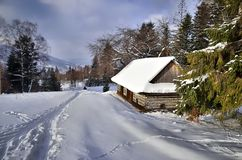 Hut in winter mountains. Snowy trail running down the valley in Beskids, Poland royalty free stock photo