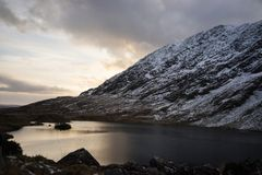 Snowy mountains and lake at sunset on Molls Gap, County Kerry, Republic of Ireland. Winter mountains and lake at sunset. Near Moll`s Gap between Kenmare and royalty free stock images