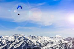 Winter mountains landscape and man paragliding Royalty Free Stock Images