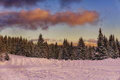 Winter mountains landscape. Sunset with dramatic clouds. Stock Photos