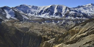 Winter in mountains: mountain ranges are covered with snow on tops, below are yellow and brown rocks, the Himalayas. Winter in the mountains: mountain ranges Royalty Free Stock Photo
