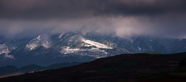 Winter mountains panorama with dramatic storm clouds, light in the dark shining on the snow mountain. Yunnan, South China stock photography