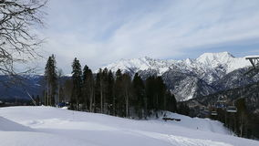 Winter mountains panorama with ski slopes and ski lifts on a cloudy day stock footage