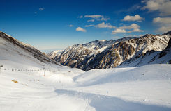 Winter mountains panorama with ski slopes and ski lifts. Skiers going down the slope under ski lift Royalty Free Stock Image
