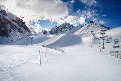 Winter mountains panorama with ski slopes and ski lifts. Skiers going down the slope under ski lift Royalty Free Stock Images