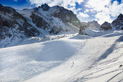 Winter mountains panorama with ski slopes and ski lifts. Skiers going down the slope under ski lift Stock Images