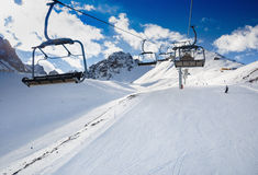Winter mountains panorama with ski slopes and ski lifts. Skiers going down the slope under ski lift Royalty Free Stock Photo
