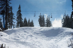 Winter mountains panorama with ski slopes and ski lifts. Sunny day with fog Royalty Free Stock Photos