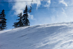 Winter mountains panorama with ski slopes and ski lifts during w. Indy weather, sunny day with fog Royalty Free Stock Image