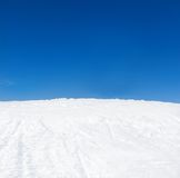 Winter mountains snow slope and blue sky Stock Images