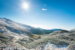 Winter mountains and sunny green valley Royalty Free Stock Images