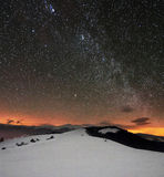 Winter mountains under starry cloudy sky. With milky way Stock Images