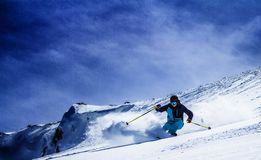 Extreme skier charging down steep slope Stock Photos