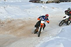 Winter MX racer on a motorcycle rides in turn of Royalty Free Stock Image