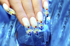 Winter nails. Aquarium design nail in the festive winter decorated with rhinestones on the blue blurred background stock photo