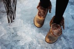 Girl in red boots walks on ice stock photo