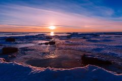 Winter nature landscape. Sunset over frozen sea. Stock Photography