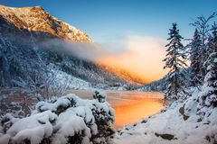 Winter nature in mountains at morning sunrise. Bright sunlight reflected in mountain lake. Snowy landscape. Winter scene. Christmas holiday background royalty free stock images