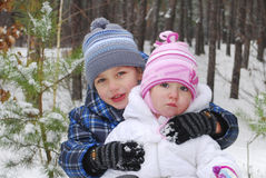 In the Winter near spruce boy hugging little girl Royalty Free Stock Photography