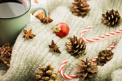 Winter and New Year theme. Christmas hot steaming cup of glint wine with spices, anise, fir cones, cookies in a shape of star, red. Candies, fir cones, pepper royalty free stock photo