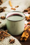 Winter and New Year theme. Christmas hot steaming cup of glint wine with spices, cinnamon, anise, cookies in a shape of star, red. Candies, fir cones, pepper stock images
