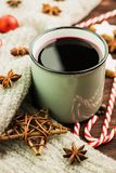 Winter and New Year theme. Christmas hot steaming cup of glint wine with spices, cinnamon, anise, cookies in a shape of star, red. Candies, fir cones, pepper stock image