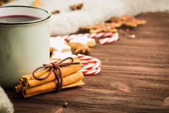 Winter and New Year theme. Christmas hot steaming cup of glint wine with spices, cinnamon, anise, cookies in a shape of star, red. Candies, fir cones, pepper royalty free stock photography