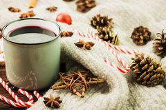 Winter and New Year theme. Christmas hot steaming cup of glint wine with spices, cinnamon, anise, cookies in a shape of star, red. Candies, fir cones, pepper stock photo