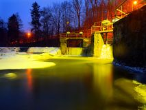 Winter night below weir. Reflection of lamps in icicle, ice and cold water. Stock Image