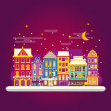 Winter night in cosy town street scene. Classic European houses. Landscape with Christmas holiday decorations. Snowfall on Christmas eve. Buildings and facades Stock Photography